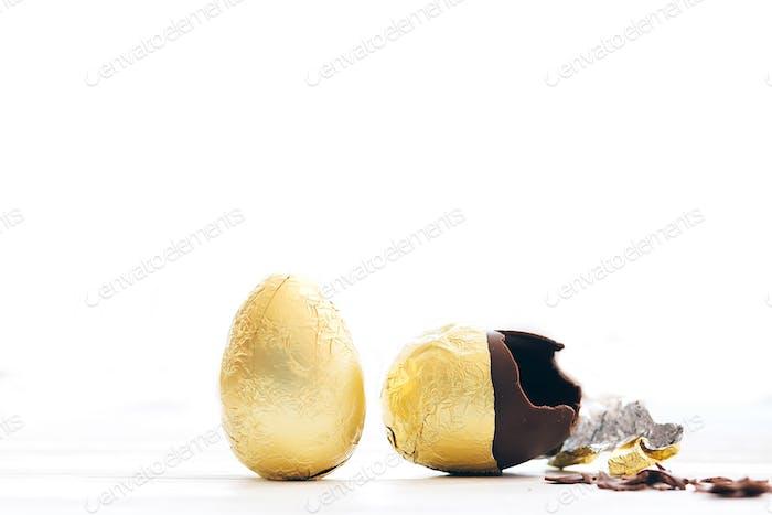 Stilvolles Osterei in goldener Folie und gebrochenem Schokoladenei mit Schokoladenstücken