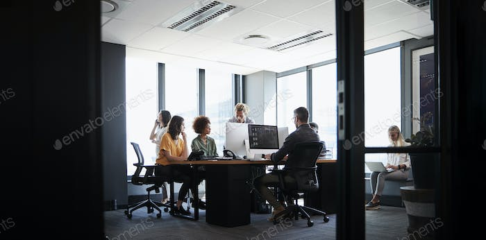 Creative business team working together in a casual office, seen from doorway, low angle
