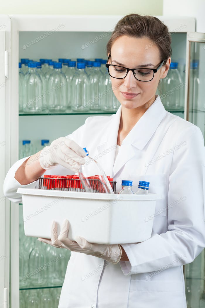 Woman holding box with laboratory equipment