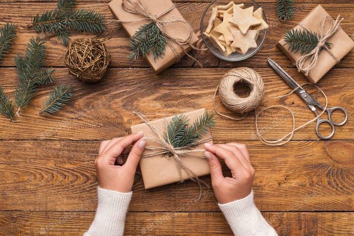 Woman decorating handmade craft Christmas gift boxes
