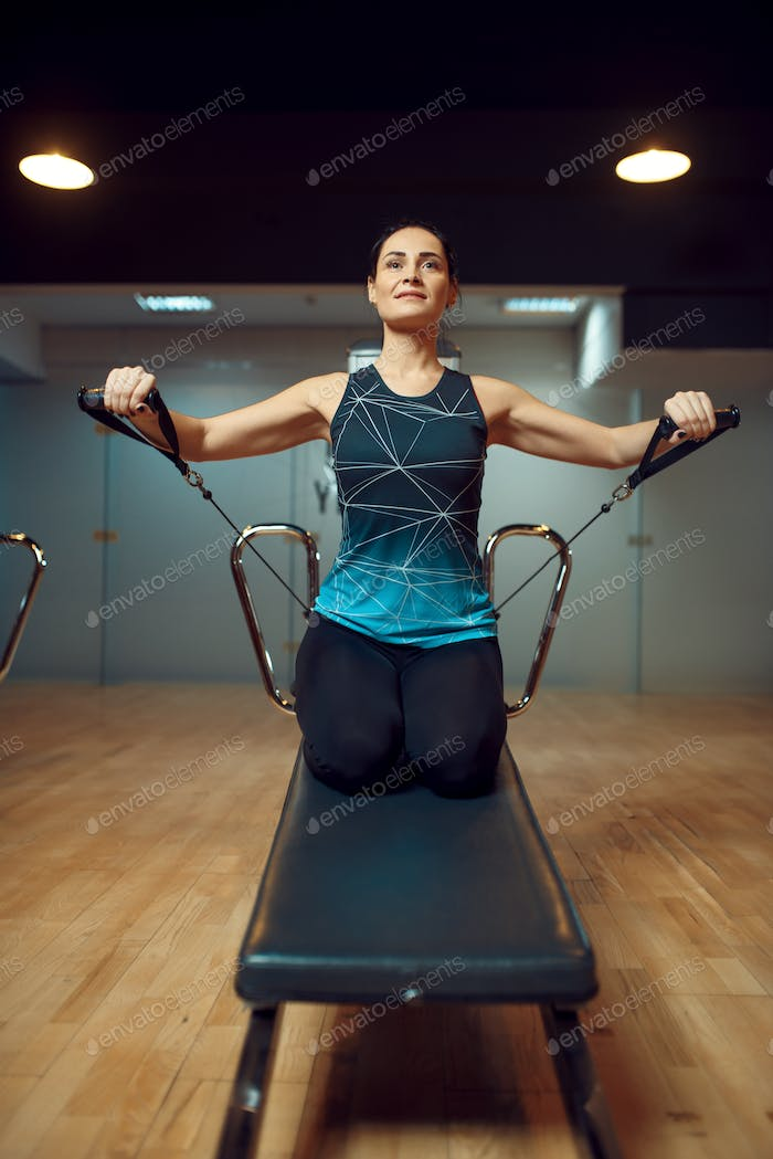 Pilates training on exercise machine in gym