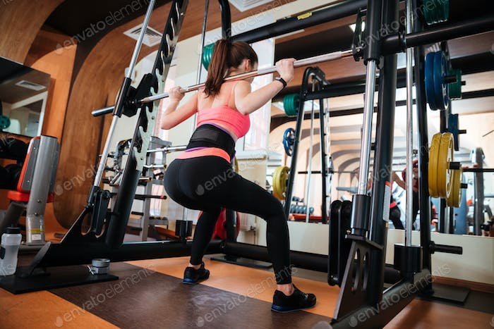 Attractive young sportswoman doing squats with barbell in gym