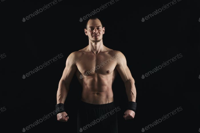 Strong athletic man showes naked muscular body