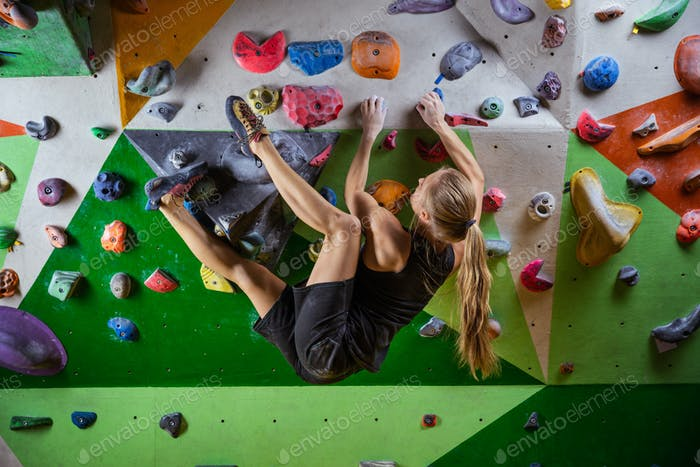 Thumbnail for Young woman bouldering on overhanging wall in climbing gym