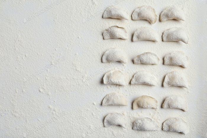 Raw handmade vareniki on table sprinkled with flour