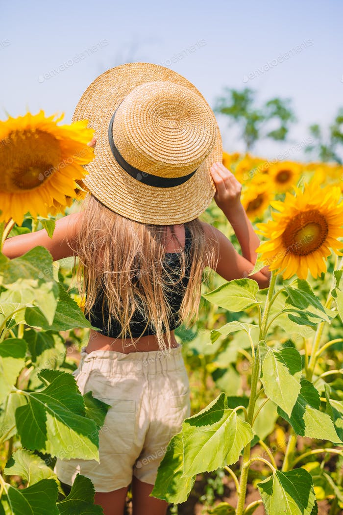 Young girl enjoying nature on the field of sunflowers