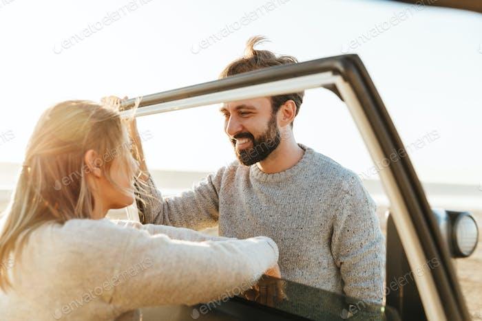 Loving couple outdoors at beach near car.