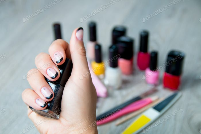 Black nail polish in female hand with tools for manicure and pedicure background. Close up.