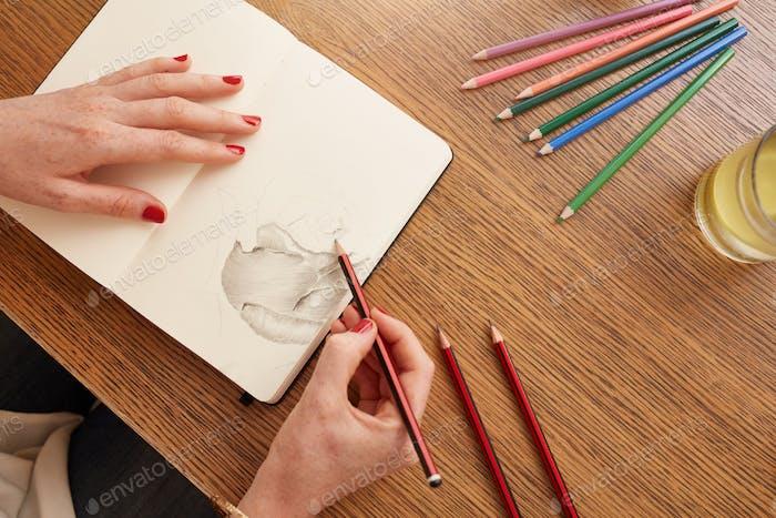 Frau skizziert eine Blume im Skizzenbuch