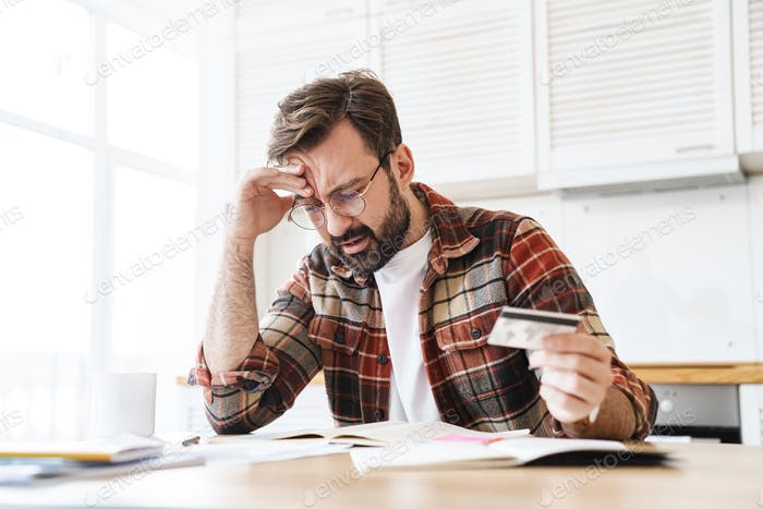 Portrait of young serious man holding credit card while working at home