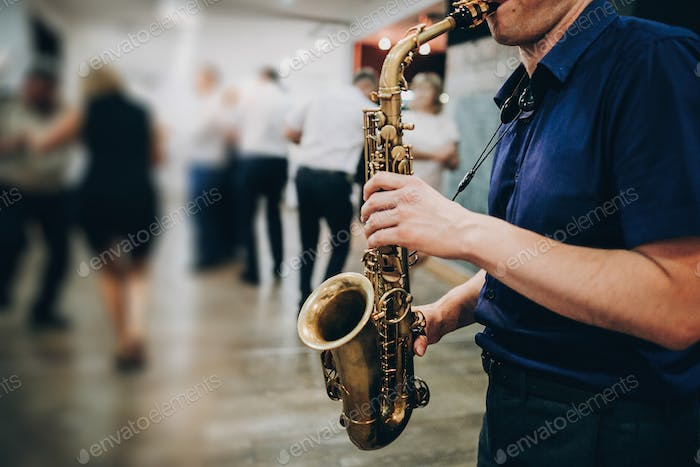 Musician playing sax at wedding reception in restaurant