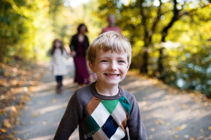 A small boy with his family on a walk in autumn forest