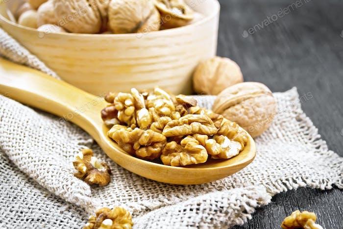 Walnuts in spoon on dark board