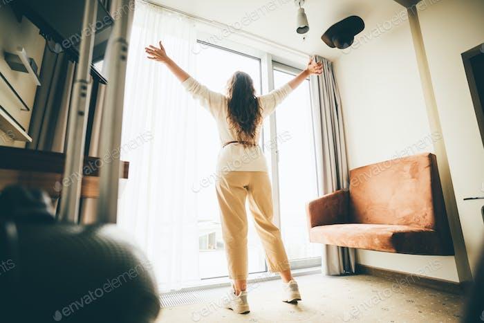 Frauen bleiben in einem Hotelzimmer am Fenster.