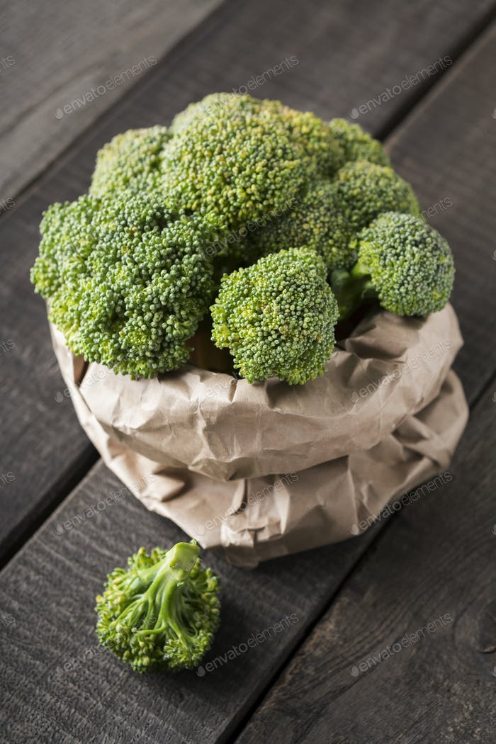 Eco coton sack full of green fresh broccoli on wood