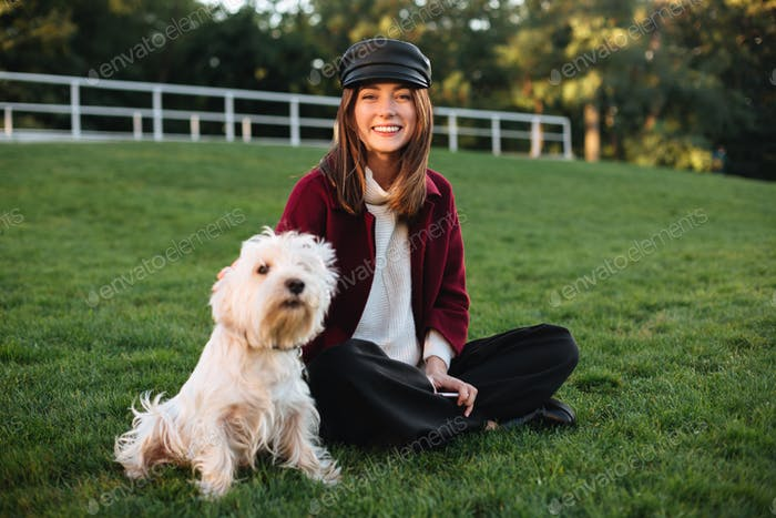 Young beautiful lady in black cap and coat sitting on grass in park with her pretty small dog