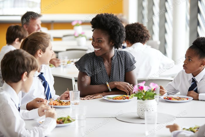 Female Teacher With Group Of High School Students In Cafeteria