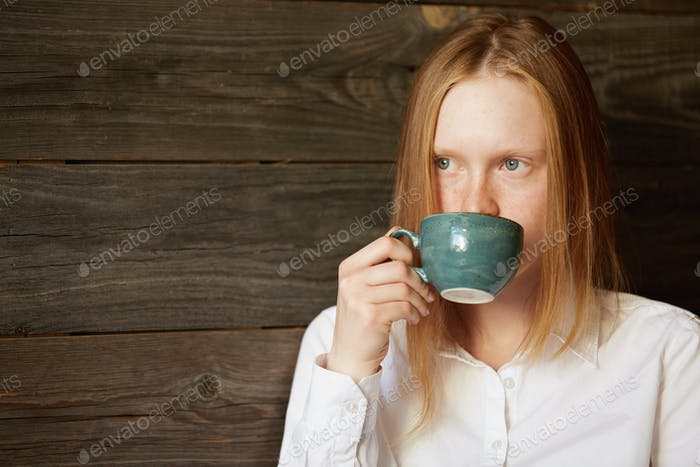 Young blond office girl drinking coffee in stylish caf�Caucasian female business-lady looking pensiv