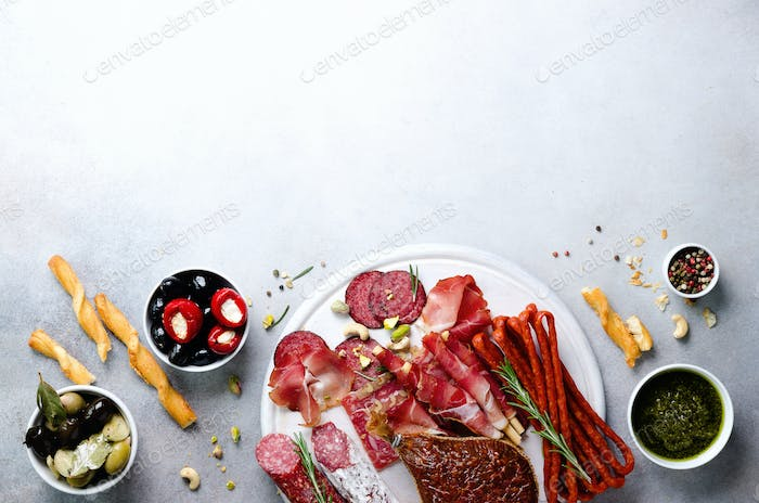 Cold smoked meat plate. Traditional italian antipasto, cutting board with salami, prosciutto, ham