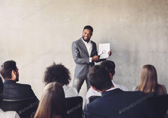 Erfolgreicher Geschäftsmann präsentiert Diagramme an Kollegen über die Ausbildung