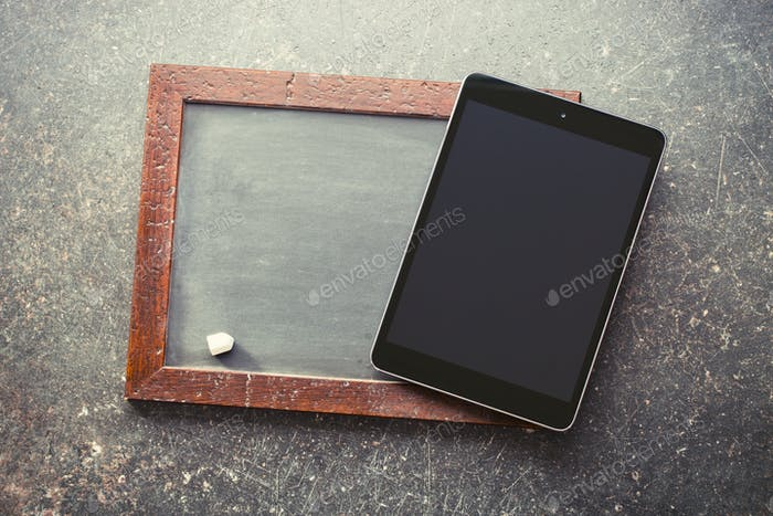 computer tablet and old chalkboard
