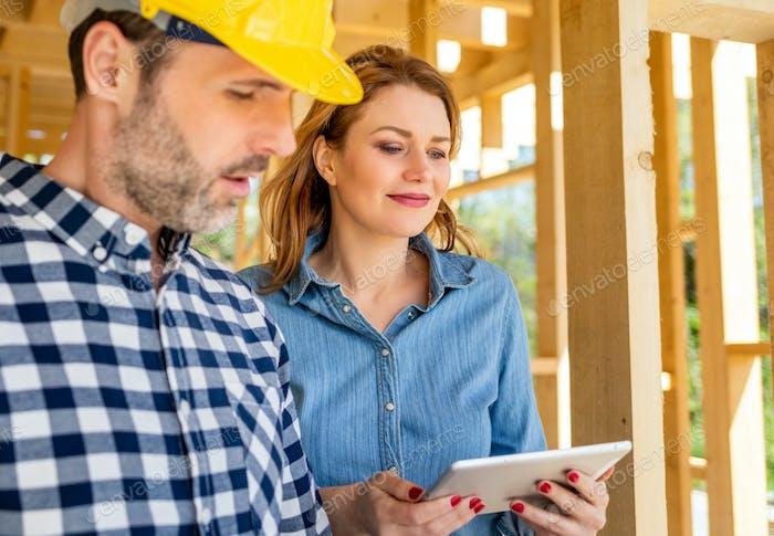 Architekt oder Ingenieur mit Bauplänen Treffen mit Eigentümer des Bauhauses auf der Baustelle