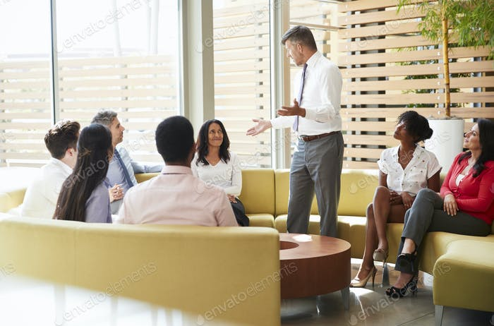 Colleagues listening to a presentation by a male manager