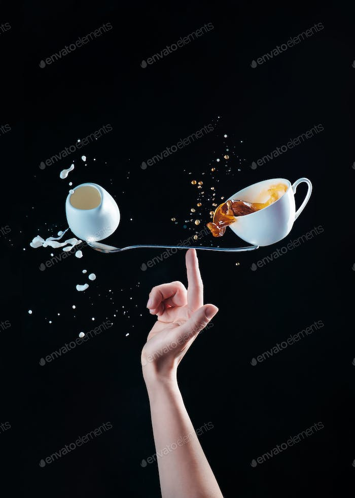 Cup of coffee and a small jug of milk balancing on a long spoon on the tip of a finger