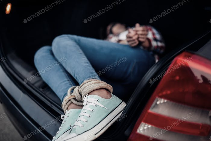 Female victim in car trunk, maniac concept