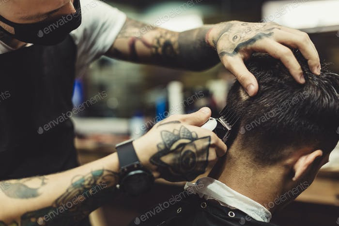 Barber shaving man in chair