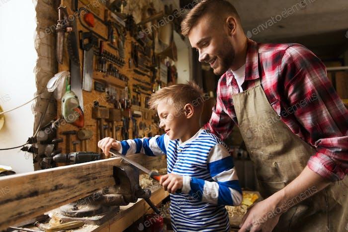 Vater und Sohn mit Raspel arbeiten in der Werkstatt