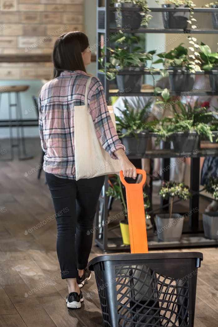 A young girl carries a cart in the store and carries an eco bag