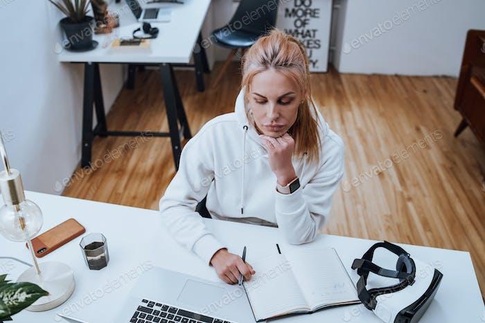 Seriöse Geschäftsfrau arbeitet mit Laptop und Notebook