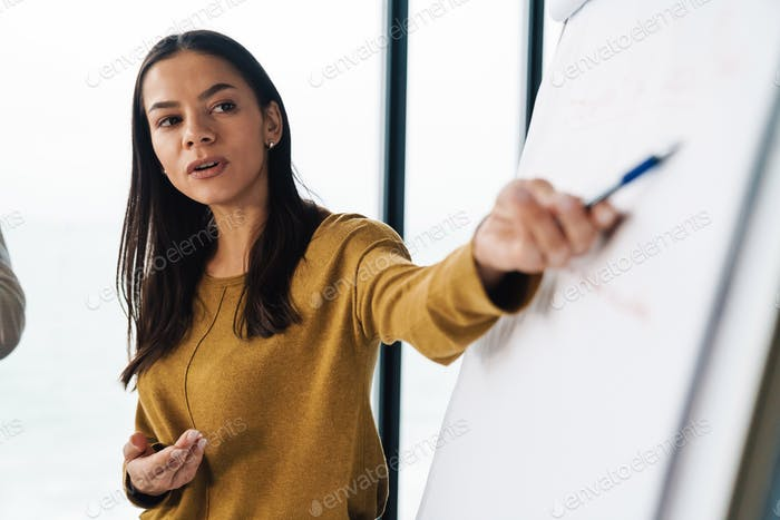Portrait of businesswoman standing by flipchart while working in office