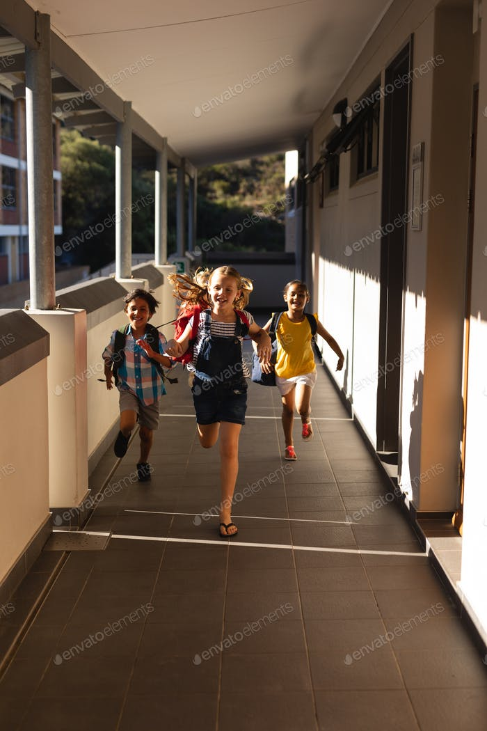 Front view of schoolkids with schoolbags running in hallway of elementary school
