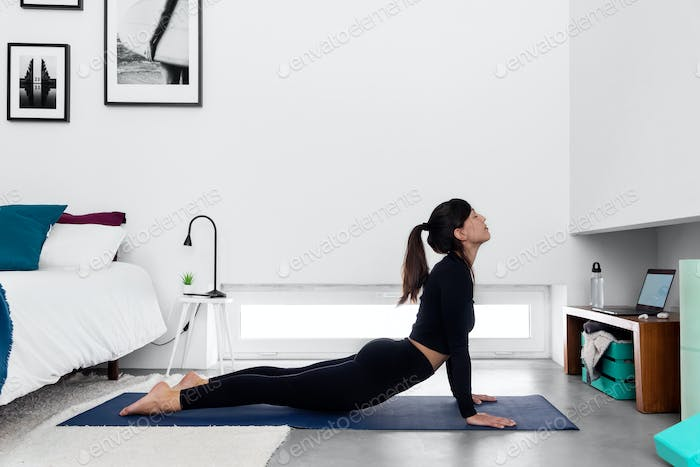 Fit woman practicing Cobra pose using online yoga training program in the laptop at home