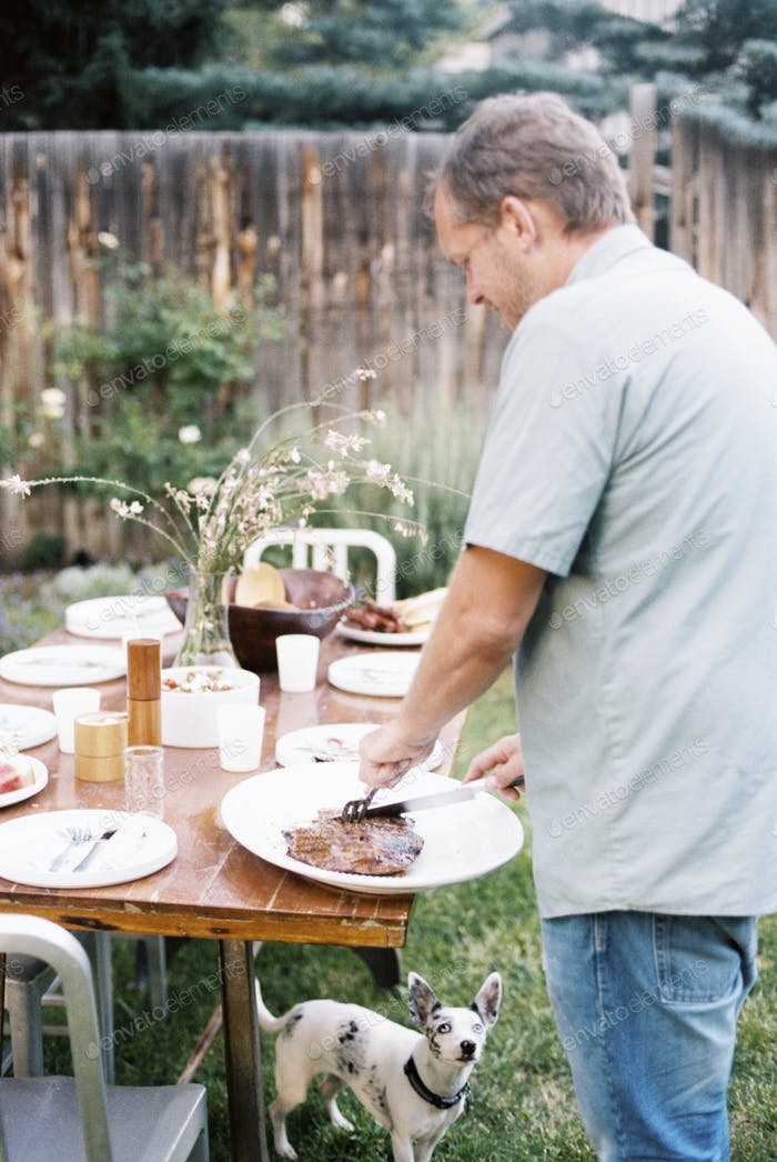 A man carving meat at a family meal in a garden, being watched by a small dog under the table.