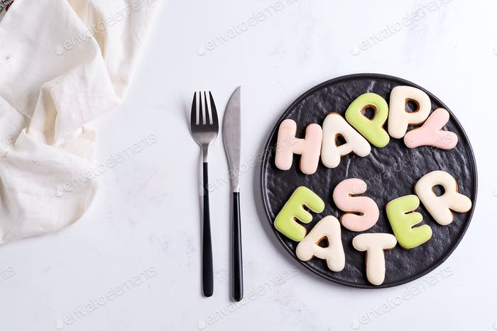Brown ceramic plate with homemade cookies letters text Happy Easter on a light grey marble