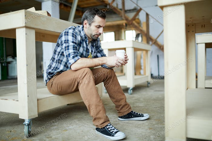 Sad carpenter drinking coffee