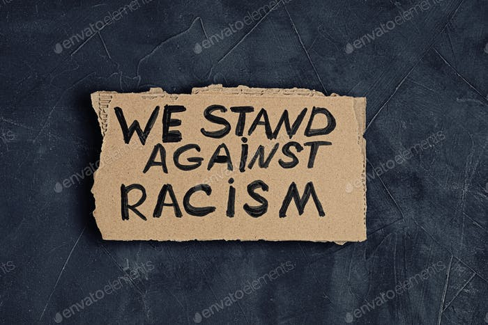 We stand against racism text on cardboard on dark background