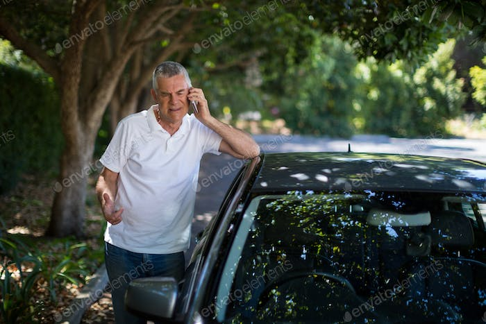 Senior man using phone by car