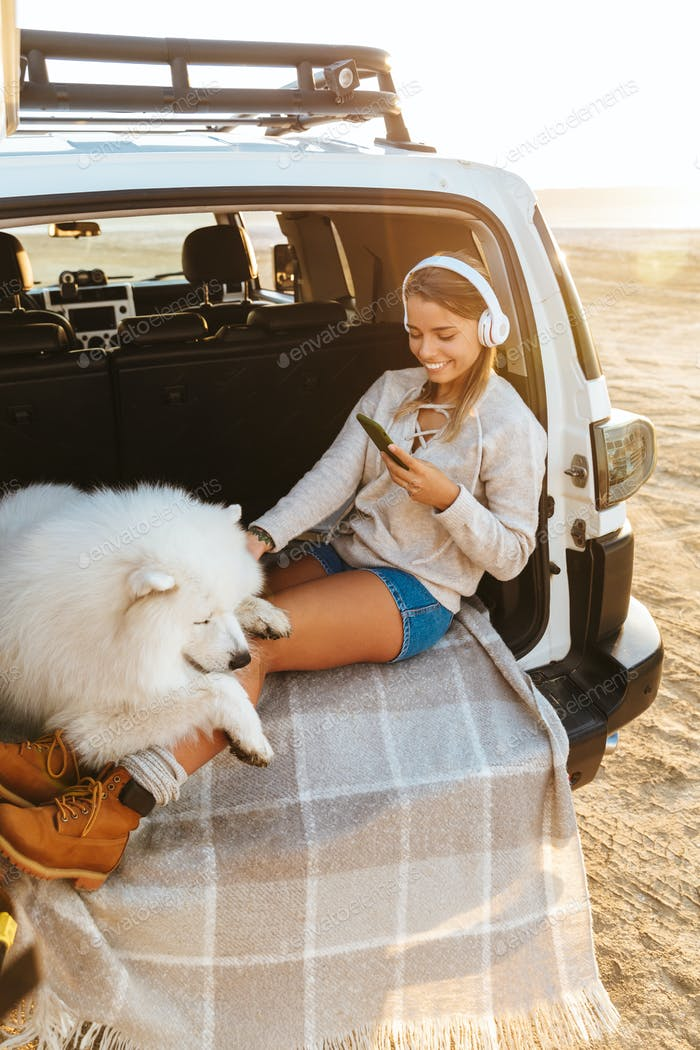 Woman with dog samoyed using mobile phone.