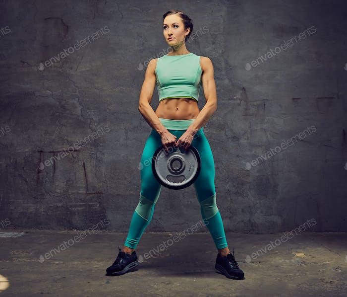 Sportliche weibliche trainiert mit Langhantelgewicht auf grauem Hintergrund.