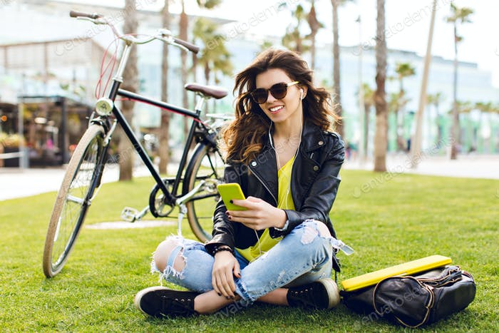 Cute brunette girl in sunglasses with ripped jean is chilling on grass on bike and palms background