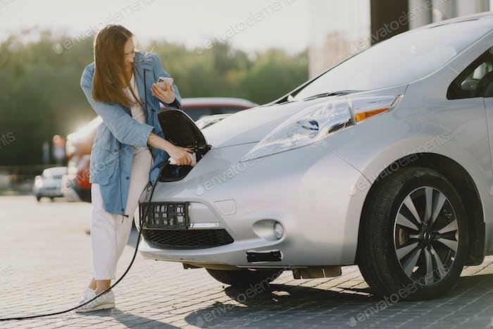 Frau lädt elektro- auto an der elektrischen Tankstelle