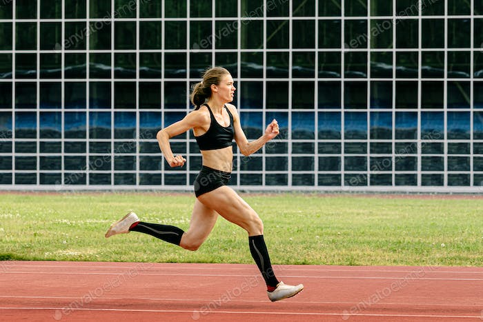 female athlete in spikes shoes running