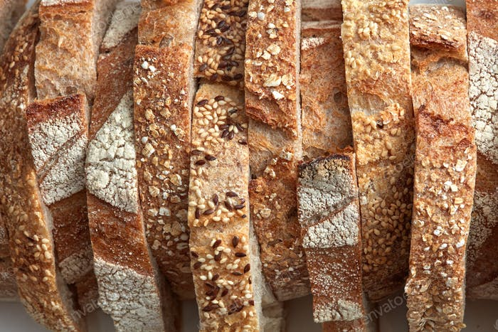 Macro photo of different pieces of fresh bread with flax seeds and sesame seeds. Healthy food. Flat