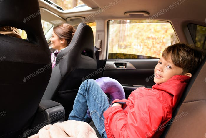 Smiling boy sitting in the back seat of car locked with safety belt and enjoying family vacation