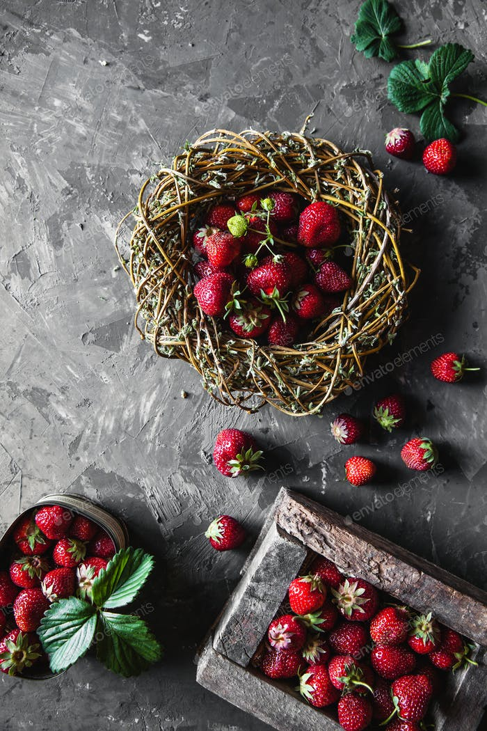 Delicious strawberries on a dark gray background in a vintage wreath. Healthy food, fruit