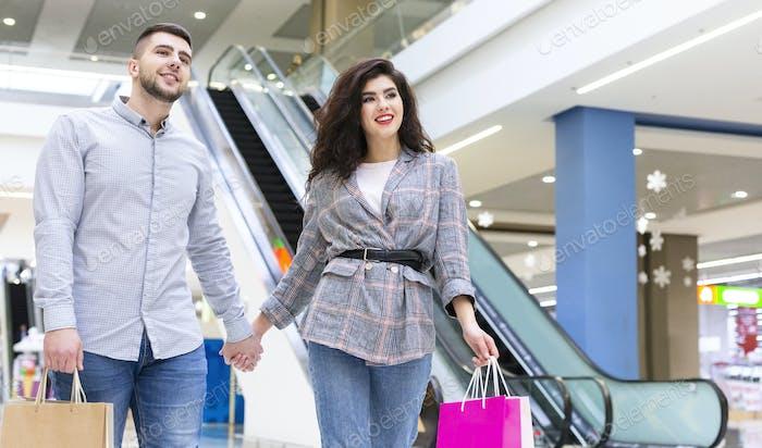 Glückliches junges Paar zu Fuß im Einkaufszentrum